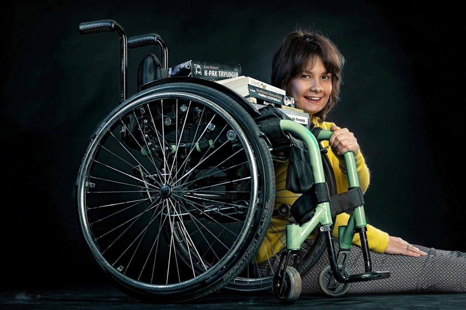 kobieta siedząca przy wózku inwalidzkim, na którym stoi stos książek