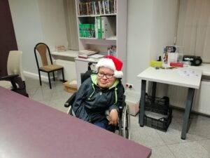 Mężczyzna. Osoba z niepełnosprawnością. Siedząca na wózku inwalidzkim przy stole w czapce mikołaja