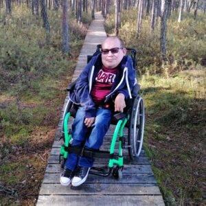 Mężczyzna. Osoba z niepełnosprawnością siedząca na wózku inwalidzkim, który stoi na mostku w lesie.