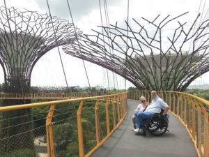 Goha i Kamil stoją na moście w Singapurze, Kamil na wózku inwalidzkim
