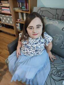 osoba niepełnosprawna siedzi na kanapie, ubrana w sukienkę